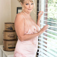 Wonderful yellow-haired granny Mia Magnusson looses her breasts and shaven cunt from lingerie